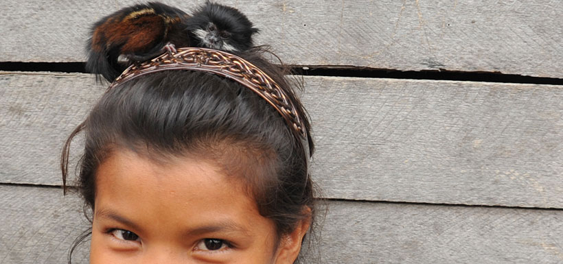 Young Peruvian girl with small monkey on her head